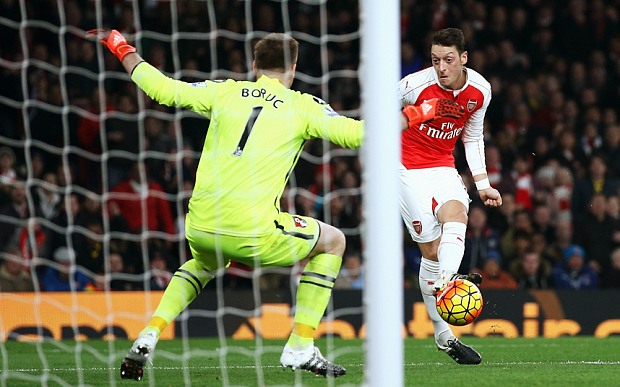 LONDON, ENGLAND - DECEMBER 28: Mesut Ozil of Arsenal scores his team's second goal past Artur Boruc of Bournemouth during the Barclays Premier League match between Arsenal and A.F.C. Bournemouth at Emirates Stadium on December 28, 2015 in London, England.  (Photo by Ian Walton/Getty Images)